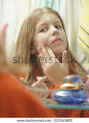 Girl with bathrobe putting cream on face - stock photo