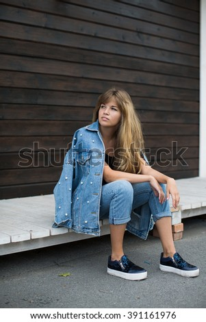 girl with beautiful hair posing in the street - stock photo