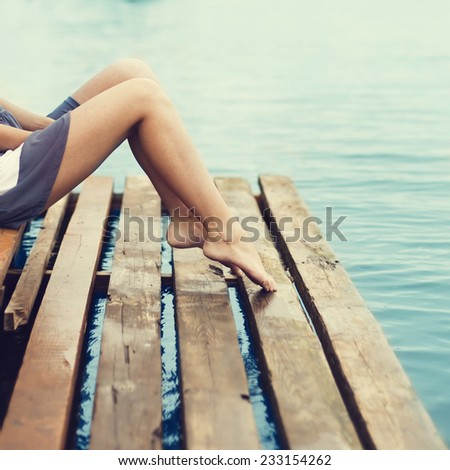 girl with beautiful legs sitting on the pier at the sea - stock photo
