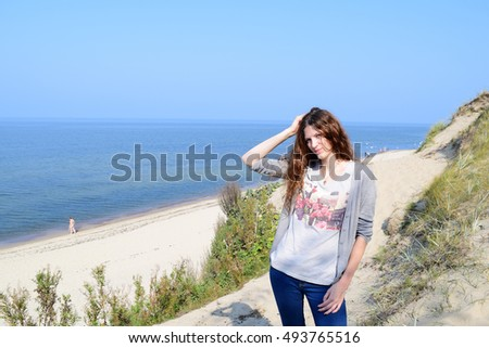 Girl with beautiful long hair standing near the sea in nature