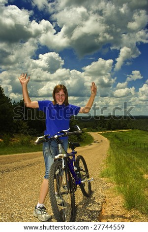 Girl with bike makes it to the top of a hill - stock photo