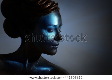 Girl with black makeup. On a dark background