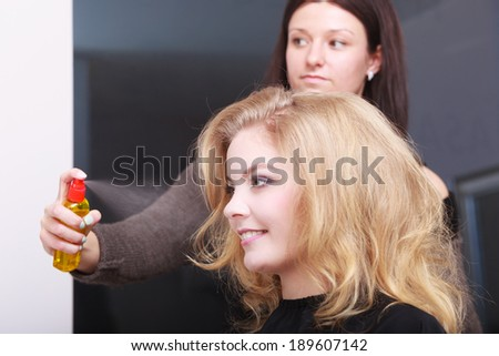 Girl with blond wavy hair by hairdresser. Hairstylist with hairspray and female client. Young woman in hairdressing beauty salon. Hairstyle. - stock photo