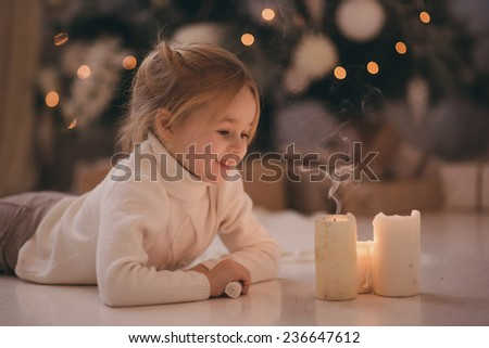 girl with blonde hair lying on the carpet blows out the candles. Christmas tree in the background. smiles - stock photo