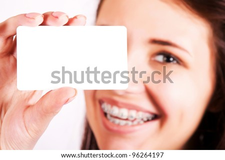 Girl with braces presenting business card - stock photo