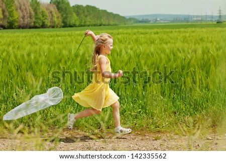 Girl with butterfly net having fun at field - stock photo