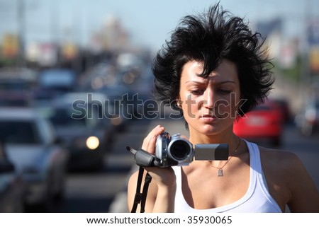 girl with camera on highway - stock photo