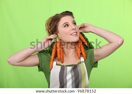 Girl with carrots as earrings - stock photo