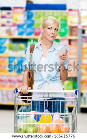 Girl with cart full of food in the shopping mall. Concept of consumerism, retail and purchase