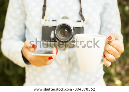 girl with cell phone, cup of coffee and old camera - stock photo