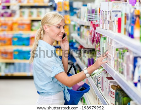 Girl with cellphone at the shop choosing cosmetics among the great variety of products. Concept of consumerism, retail and purchase - stock photo