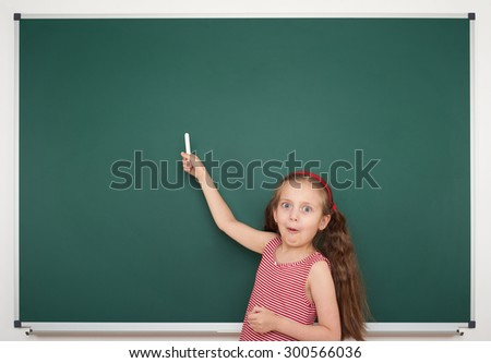 girl with chalk write on school board
