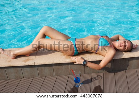 girl with cocktail near pool