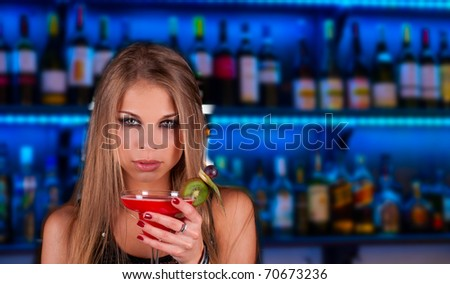 Girl with cocktail on bar counter background