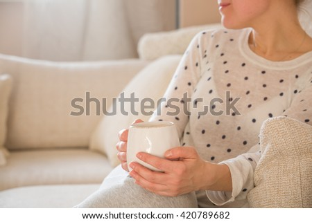 Girl with coffee mug sitting on the sofa indoors. Woman drinking a cup of  coffee or tea sitting cozy at home. Relax and rest. - stock photo
