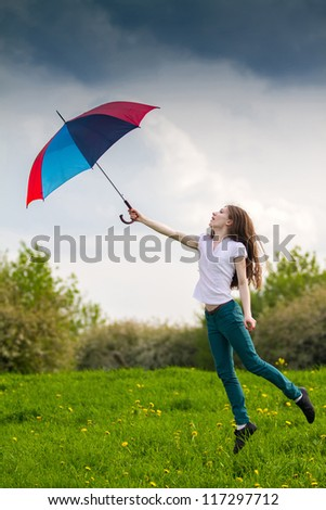 Girl with colored umbrella jumping in a green meadow - stock photo
