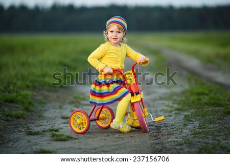 girl with colorful dress on the bicycle - stock photo