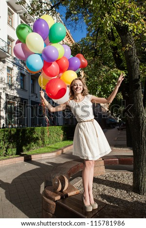 girl with colorful latex balloons keeping her hands, urban scene, outdoors - stock photo
