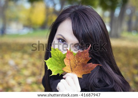 Girl with colorful leaves in the park. - stock photo
