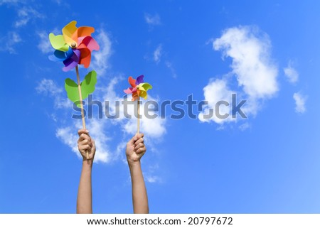 girl with colorful small windmills, concept of wind energy (blue sky) - stock photo