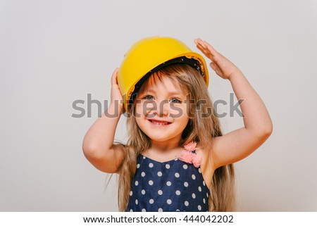 girl with construction tools. Little girl in polka-dot dress. little girl in a helmet. Child protection and safety.  baby building. little girl making repairs. little girl in a helmet laughing