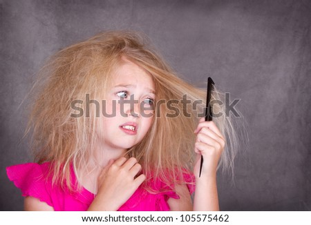 Girl with crazy tangled hair trying to comb it out - stock photo