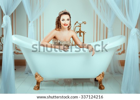 Girl with crown lies in the bath and smiling. Her bright makeup, it's fashion style. - stock photo