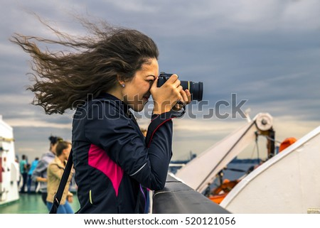 Girl with curly hair is taking a picture