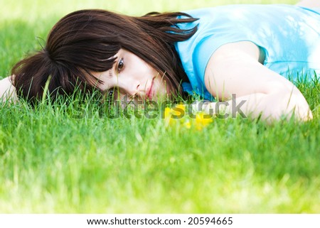 Girl with dandelions lying on the green lawn