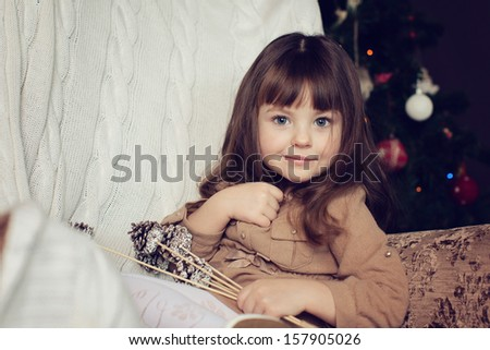 girl with dark hair sitting in a chair. Christmas tree in the background. smiles - stock photo