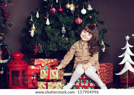 girl with dark hair sitting on a box with gifts. Christmas tree in the background. smiles - stock photo