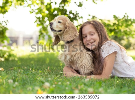 girl with dog lying on a grass - stock photo