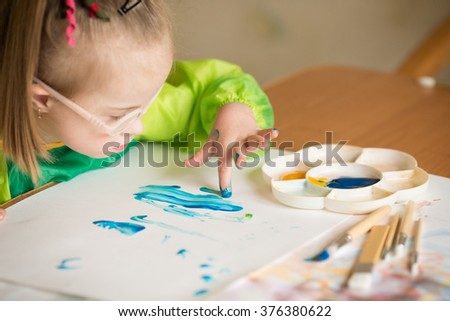 Girl with Down syndrome covered in paint when drawing