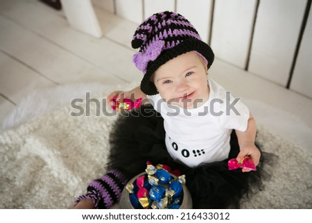Girl with Down syndrome eating candy on a holiday halloween - stock photo