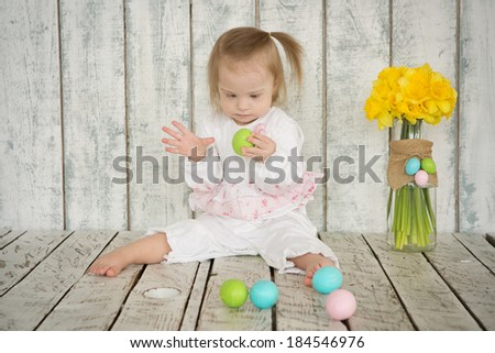 Girl with Down syndrome is holding Easter eggs