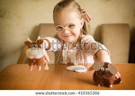 Girl with Down syndrome playing Felt animals developing fine motor skills of fingers - stock photo