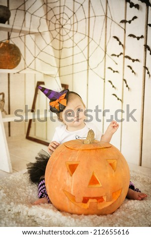 Girl with Down syndrome sitting near big pumpkin on Halloween - stock photo