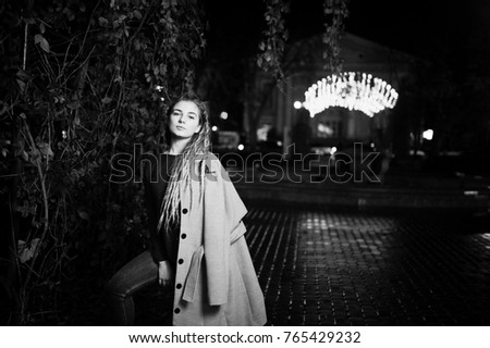 Girl with dreadlocks walking at night street of city against garland lights.