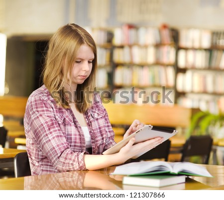girl with electronic pad in library - stock photo