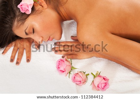 Girl with eyes closed laying on a towel with roses - stock photo