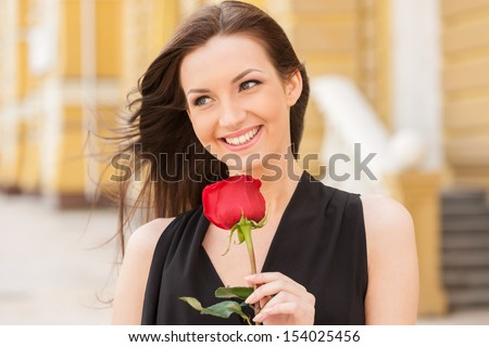 Girl with flower. Beautiful young woman holding red rose and smiling - stock photo