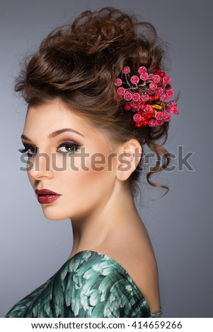 Girl with flowers in her hair. The girl's face. Red flowers. Pretty brunette female model face with artistic make up.