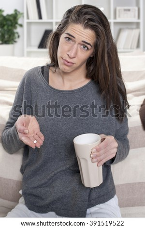 Girl with flu sitting in the room and takes pill - stock photo