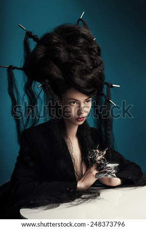 girl with fluffy hair sitting at the table - stock photo