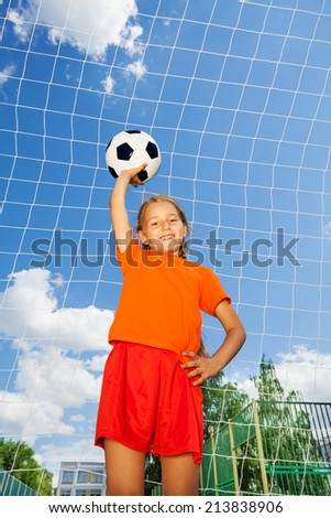 Girl with football stands in front woodwork net - stock photo