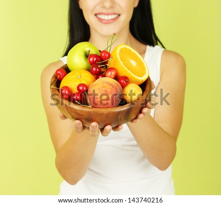Girl with fresh fruits on green background
