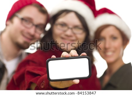 Girl with Friends and Santa Hats Holding Blank White Smart Phone - Ready for Your Own Message. - stock photo