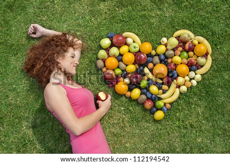 Girl with fruit lying on the grass - stock photo