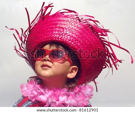 girl with funny tropical hat, two years old, on gray background - stock photo