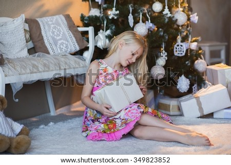 Girl with gift box in hands is happy considers preparation for the holiday, packaging, boxes, Christmas, New Year, lifestyle, holiday, vacation, waiting for santa